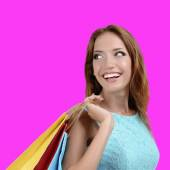 Beautiful young woman with shopping bags on pink background — Stock Photo