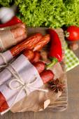 Assortimento di salsicce sottili, senape in ciotola e spezie su tagliere, su fondo in legno — Foto Stock