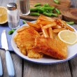 Breaded fried fish fillets and potatoes with asparagus and sliced lemon on plate and wooden planks background — Stock Photo #65343817