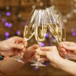 Clinking glasses of champagne in hands on bright lights background — Stock Photo #65343507