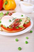 Sandwich with poached eggs, bacon and vegetables on plate on wooden background — Stock Photo