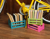 Bicycle with books in crate on wooden wall background — Stock fotografie