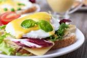 Toast with egg Benedict and tomato on plate on wooden table — 图库照片