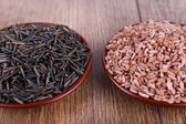 Red and black rice in pales on wooden background — Stock Photo