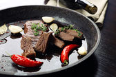 Steak in frying pan on table close up — Stock Photo