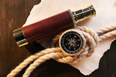 Marine still life spyglass, compass rope and sheet of paper on wooden background — Stock Photo