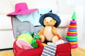 Suitcase packed with clothes and child toys on fur rug and white sofa background — Stock fotografie