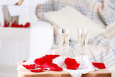 Champagne glasses and rose petals for celebrating Valentines Day — Stock Photo
