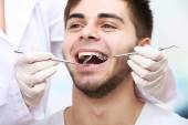 Examine of young man by dentist on light blurred background — Photo