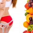 Beautiful young woman measuring her body with tape and fruits near her isolated on white — Stock Photo #65373817