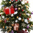 Decorated Christmas tree on floor on light wall background — Stock Photo #65403455