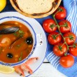 Tasty soup with shrimps, mussels, tomatoes and black olives in bowl on wooden background — Stock Photo #65403567