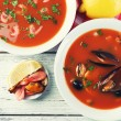 Tasty soup with shrimps, mussels, tomatoes and black olives in bowl on wooden background — Stock Photo #65403587