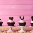 Delicious Valentine Day cupcakes on pink wooden background — Stock Photo #65405753