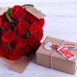 Bouquet of red roses wrapped in paper and present box on wooden background — Stock Photo #65406765
