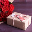 Bouquet of red roses wrapped in paper and present box on wooden background — Stock Photo #65406781