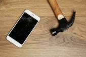 Broken iPhone with hammer on wooden background — Stock Photo