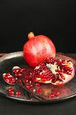 Juicy ripe pomegranates on metal plate, on dark background — Foto Stock