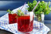 Pomegranate drink in glasses with mint and slices of lime on napkin on color wooden background — Stock Photo