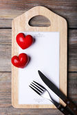 Cutting board with menu sheet of paper and hearts on rustic wooden planks background — Stock Photo