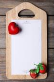 Cutting board with menu sheet of paper, heart and strawberry on rustic wooden planks background — Stock Photo