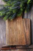 Cutting board with Christmas decoration on wooden planks background — Stok fotoğraf