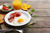 Bacon and eggs on rustic wooden planks background — Photo