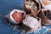 Различные виды риса в мешках на деревянных фоне — Стоковое фото