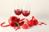 Composition with red wine in glasses, red roses, ribbon and decorative hearts on light background — Stock Photo