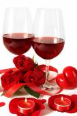 Composition with red wine in glasses, red roses, ribbon and decorative hearts on light background — Stock fotografie