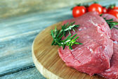 Raw beef steak with rosemary and cherry tomatoes on cutting board on wooden background — Stock Photo