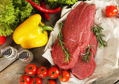Raw beef steak on paper with vegetables and greens on wooden background — Stock Photo