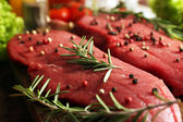 Raw beef steak with spices and greens on table close up — Stock Photo
