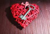 Key on wicker decorative heart on wooden background — Stock Photo