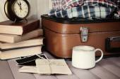 Vintage suitcase with clothes and books on wooden background — Stock Photo