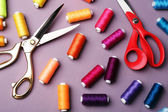 Multicolor sewing threads with scissors on wooden background — Stock Photo