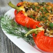 Stuffed red peppers with greens on plate on wooden table — Stock Photo #65420267