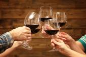 Clinking glasses of red wine in hands on rustic wooden planks background — Stock Photo