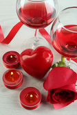 Composition with red wine in glass, red roses and decorative heart on color wooden background — Stockfoto