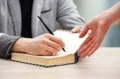 Author signing autograph in own book at wooden table on light blurred background — Stock Photo