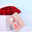 Bouquet of red roses in textile box with present on wooden background — Stock Photo #65504471