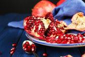 Juicy ripe pomegranates on wooden table, on dark background — Stock Photo