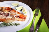 Dish of Pangasius fillet with spices and vegetables on plate and wooden table background — Stock Photo
