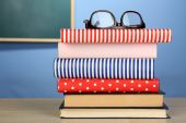 Stack of books with glasses on wooden desk, on colorful wall and blackboard background — 图库照片