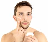 Handsome young man applying cream lotion on face isolated on white — Stock Photo