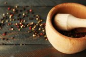 Mixture of peppers in mortar on wooden background — Stock Photo