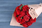 Bouquet of red roses with tag wrapped in paper on wooden background — Stock Photo