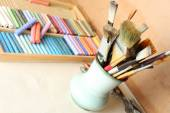 Paintbrushes with colorful chalk pastels in box on wooden background — Stock Photo