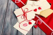 Love letters with red ribbon on wooden background — Stock Photo