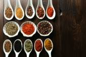 Different kinds of spices in bowls and spoons, close-up, on wooden background — Stock Photo